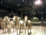 Glassed in bronze horses look like they are running towards the camera.