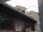 Concrete housing is built up against the side of Yuyuan Garden